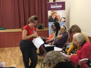 Becki Short: Music for the Mind practitioner, giving out instruments and songbooks to those attending